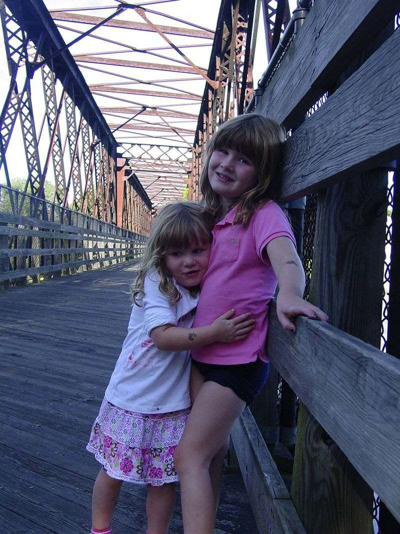 Ella and Maisie hugging on bridge